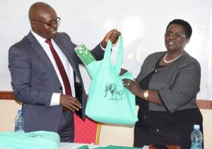 Managing Director Professor Thomas Kipkurgat (Left) hands a gift to Uasin Gishu Chief Executive Committee member in charge of Trade and ICT Dr. Emily Kogos